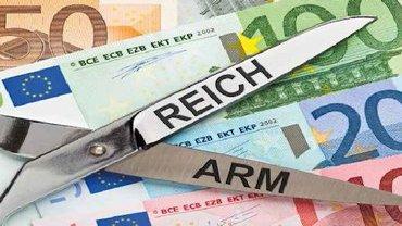 """Foto mehrerer Geldscheine und einer geöffneten Schere mit den Begriffen """"Reich"""" und """"Arm"""" auf den Scherenblättern"""