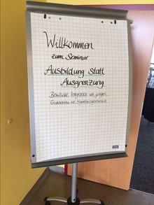 """Flipchart mit der Aufschrift """"Willkommen zum Seminar Ausbildung statt Ausgrenzung; Berufliche Integration von jungen Erwachsenen mit Migrationsgeschichte"""""""