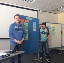 zwei Seminarteilnehmer vor einer Pinwand