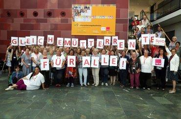 """Gruppenbild von Teilnehmer*innen der 14. Frauen-Alterssicherungskonferenz, die einzelne Buchstabenschilder hochhalten, die zusammen genommen """"Gleiche Mütterrente für alle!"""" ergeben"""