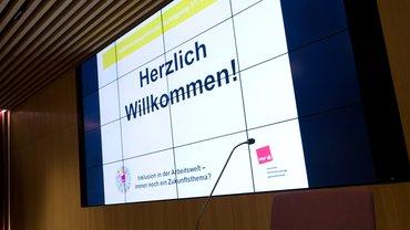 """Vordergrund: Podiumstisch mit Mikrofon; Hintergrund: Beamerleinwand mit """"Herzlich-Willkommen"""""""