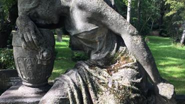 Statue, die ihren Kopf auf den Unterarm legt, der auf einem Gefäß liegt