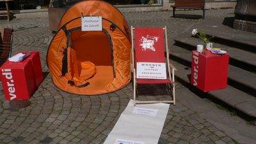 aufgebautes Zelt, Liegestuhl und mehrere ver.di-Sitzhocker mit angehängten Hinweisen auf die Wohnungsnot