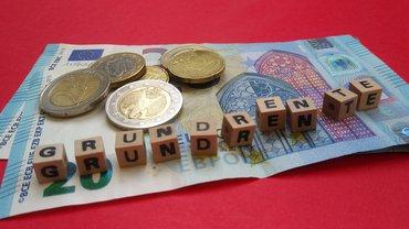 """Geldscheine und Münzen, auf denen Buchstabenwürfel liegen, die das Wort """"Grundrente"""" darstellen"""
