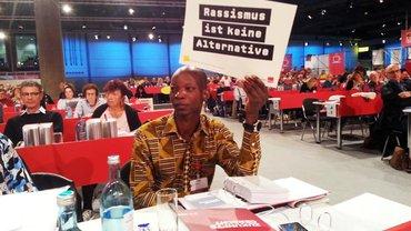 """Kollege während des ver.di-Bundeskongresses, der ein Schild hochhält, auf dem steht: """"Rassismus ist keine Alternative"""""""
