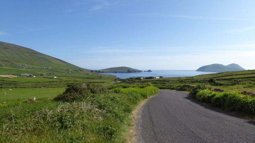 Straße, die durch große Wiesenfelder auf eine Küste zugeht