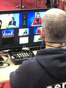 Blick auf Monitor mit Videokonferenz über die Schulter einer im Vordergrund sitzenden Person.