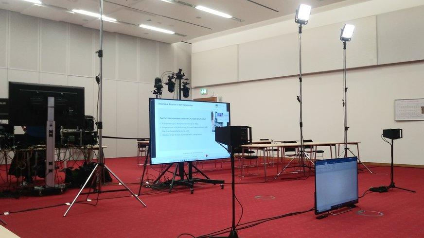 ein Raum voller Technik, wie z.B. Fernsehbildschirme und große Spots
