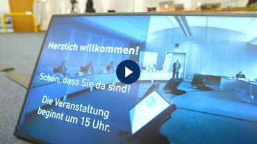 Blick auf einen am Boden stehenden Bildschirm, auf dem ein Sitzungsraum mit Personen bei einer Videokonferenz zu sehen ist
