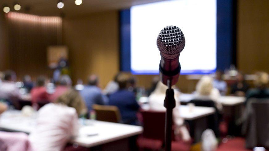 Vordergrund: Mikrofon; Hintergrund: verschwommener Blick auf Tagungsteilnehmer*innen und Beamerleinwand